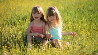 Cute kids sitting on grass and laughing