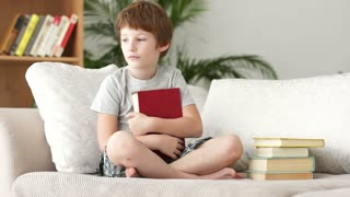 Cute little boy sitting on sofa holding book and showing thumb up