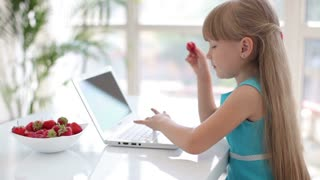 Cute little girl eating strawberries at table with laptop in front of her and looking at camera with smile