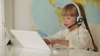 Cute little girl in headset sitting at table using laptop and touchpad and smiling