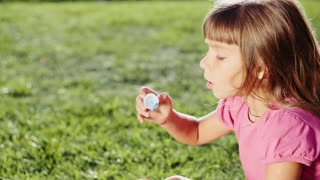 Cute little girl is blowing soap bubbles in the garden outdoors on a sunny day. Slow Motion 240 fps. Happy childhood concept. Child is playing in bright sun light.