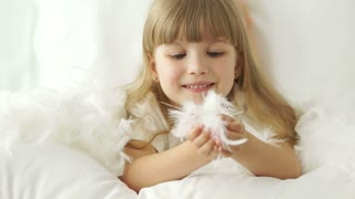 Cute little girl lying in bed laughing and playing with pillow feathers