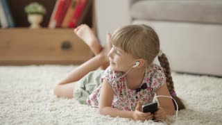 Cute little girl lying on floor listening to music on mp3 player and smiling at camera