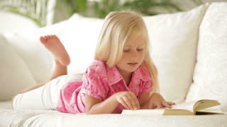 Cute little girl lying on sofa reading book and smiling