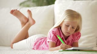 Cute little girl lying on sofa writing in notebook and smiling