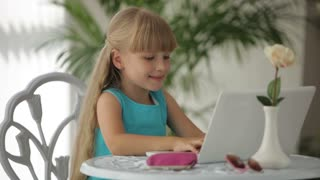Cute little girl siting at table using laptop opening her wallet and taking out credit card