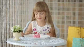 Cute little girl sitting at cafe eating cake and smiling at camera