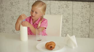 Cute little girl sitting at kitchen table and pouring milk into glass