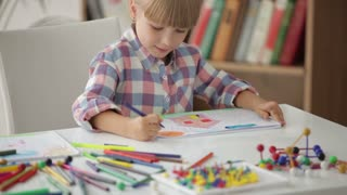 Cute little girl sitting at table drawing with colored pencils and showing her painting at camera