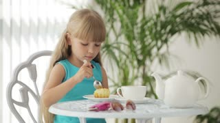 Cute little girl sitting at table eating cake and smiling at camera
