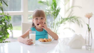 Cute little girl sitting at table eating cakes and drinking milk and laughing at camera