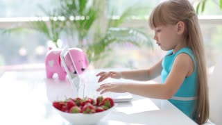 Cute little girl sitting at table with bowl of strawberries and using laptop