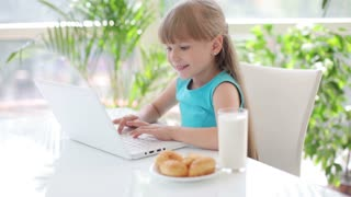 Cute little girl sitting at table with glass of milk and plate of cakes using laptop and laughing at camera
