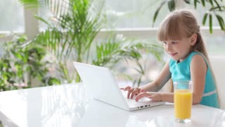 Cute little girl sitting at table with laptop drinking juice and laughing at camera