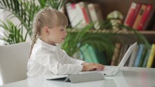 Cute little girl sitting at table with laptop turning around and smiling at camera