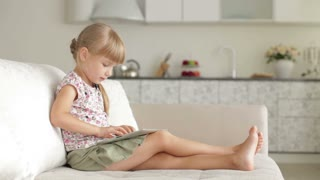 Cute little girl sitting on couch using touchpad and smiling at camera