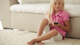 Cute little girl sitting on floor and pushing buttons on remote control