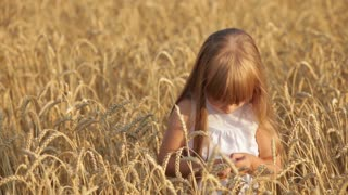 Cute little girl standing in wheat giving thumb up and smiling happily at camera
