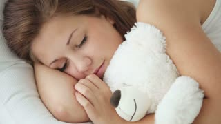 Cute sleeping girl hugging teddy bear and smiling