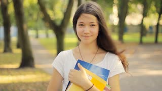 Cute student smiling and holding textbooks, back to school, funny, wind