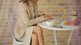 Cute woman sitting at cafe using laptop and smiling at camera