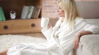 Cute young woman in bathrobe sitting on floor drinking from cup looking at camera and smiling. Panning camera