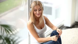 Cute young woman in headset sitting by window using cellphone and smiling