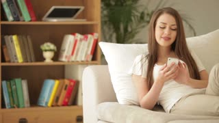 Cute young woman relaxing on sofa using mobile phone and smiling