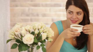 Cute young woman sitting at cafe drinking tea looking at camera and smiling. Panning camera