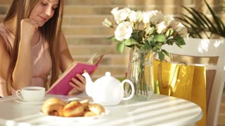 Cute young woman sitting at cafe reading book closing it looking at camera and smiling. Panning camera