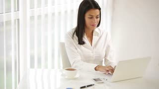 Cute young woman sitting at office desk using laptop closing it looking at camera and smiling