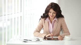 Cute young woman sitting at office table using touchpad and cellphone and smiling at camera