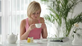 Cute young woman sitting at table drinking tea and smiling at camera