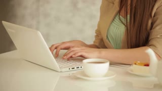 Cute young woman sitting at table using laptop looking at camera and smiling