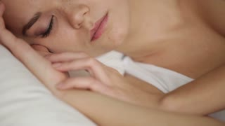 Cute young woman sleeping in bed and smiling in her sleep. Panning camera