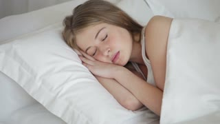 Cute young woman sleeping in bed moving and smiling in her sleep. Panning camera