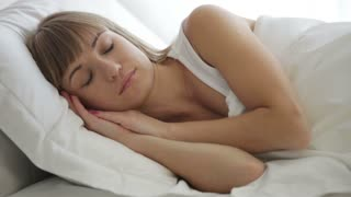 Cute young woman sleeping in bed opening her eyes and smiling