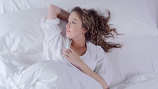 Cute young woman sleeping in bed waking up and smiling at camera.