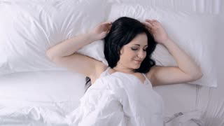 Cute young woman sleeping in bed waking up .