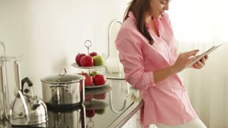 Cute young woman standing in kitchen using touchpad and smiling. Panning camera