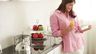 Cute young woman standing in kitchen using touchpad drinking juice looking at camera and smiling. Panning camera
