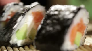 Cutting sushi rolls. Beautiful macro with shallow dof.