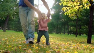 Dad walking with little baby boy on golden foliage in the park in slow motion