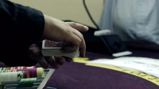 Dealer Fanning and Shuffling the Cards Over a Purple Table