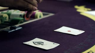 Dealer Showing Off Deck with Two Cards on Purple Table