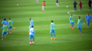 Defocused slow motion shot of soccer players' warm-up before the game.