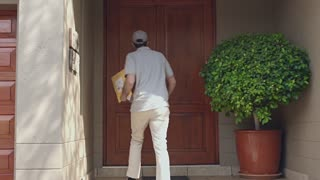 Delivery man delivering package to a happy couple at home.