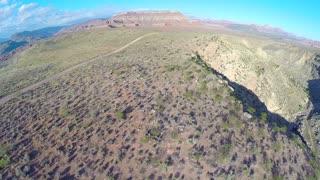 Desert landscape aerial flyover dropping down
