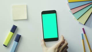 Designer is Using Mobile Phone with Green Screen in Landscape Mode. Top View.