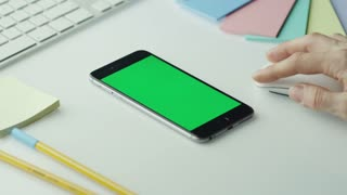 Designer is Using Mobile Phone with Green Screen in Portrait Mode. Top View.